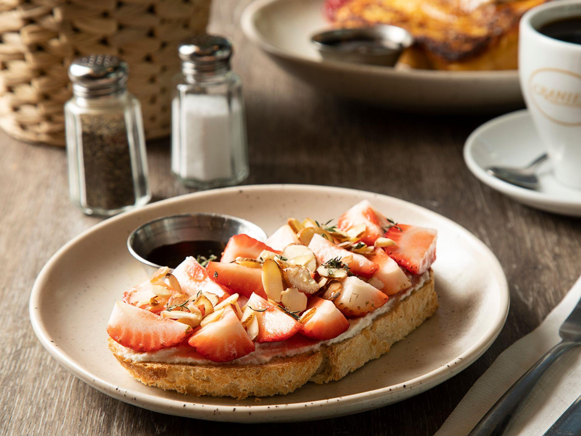 French toast with strawberries and assorted nuts with maple syrup