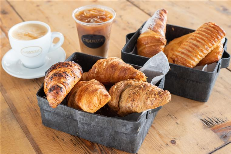 bread and pastries on a wood table with a cup of hot coffee and a cup of iced coffee.