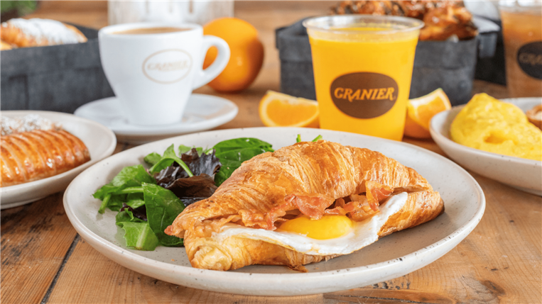 Croissant sandwich with egg and bacon. Assorted other breakfast items around it on a wood table.