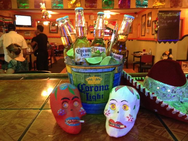 two masks in front of a bucket of corona