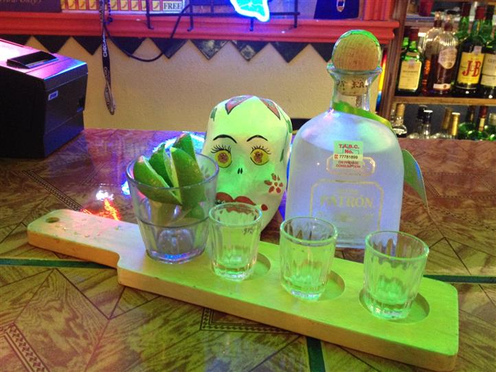 several shot glasses with lime and tequila