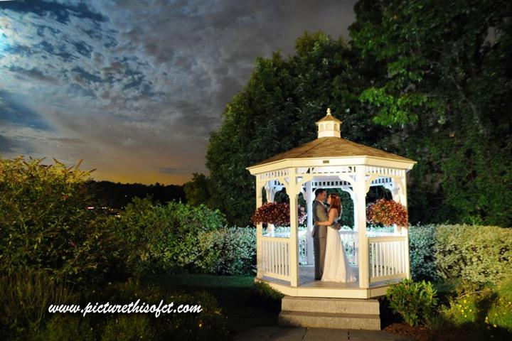 couple kissing in the outdoor gazebo during sunset