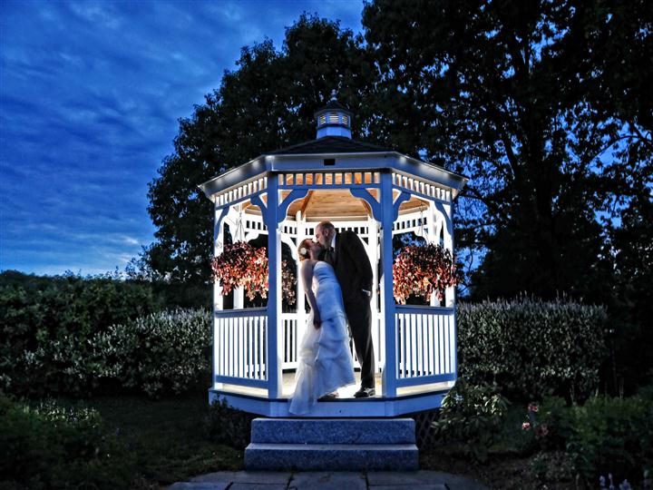 couple kissing in the outdoor gazebo at sunset