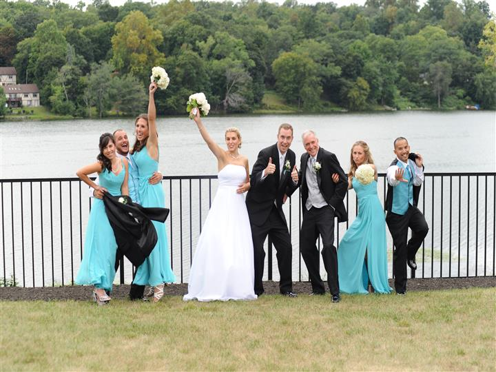 bridesmaids and groomsmen posing for the camera in front of the lake