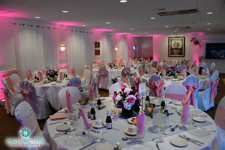 large banquet room with several tables set up with plates and silverware with a bouquet in the middle