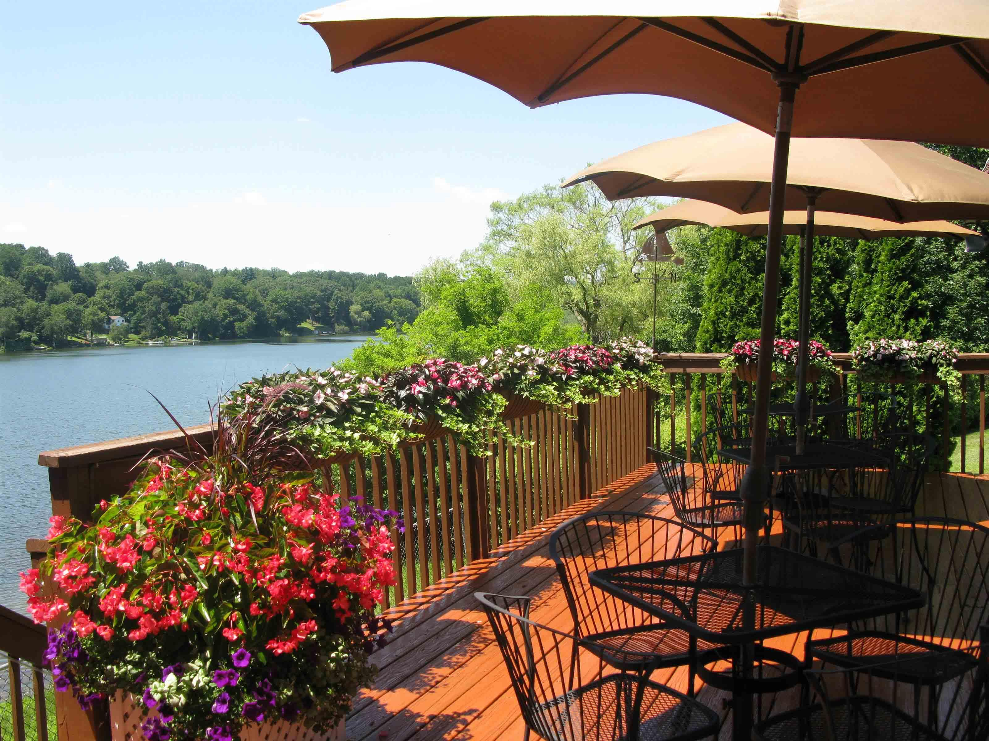 outdoor patio next to a lake with tables, chairs and flowers