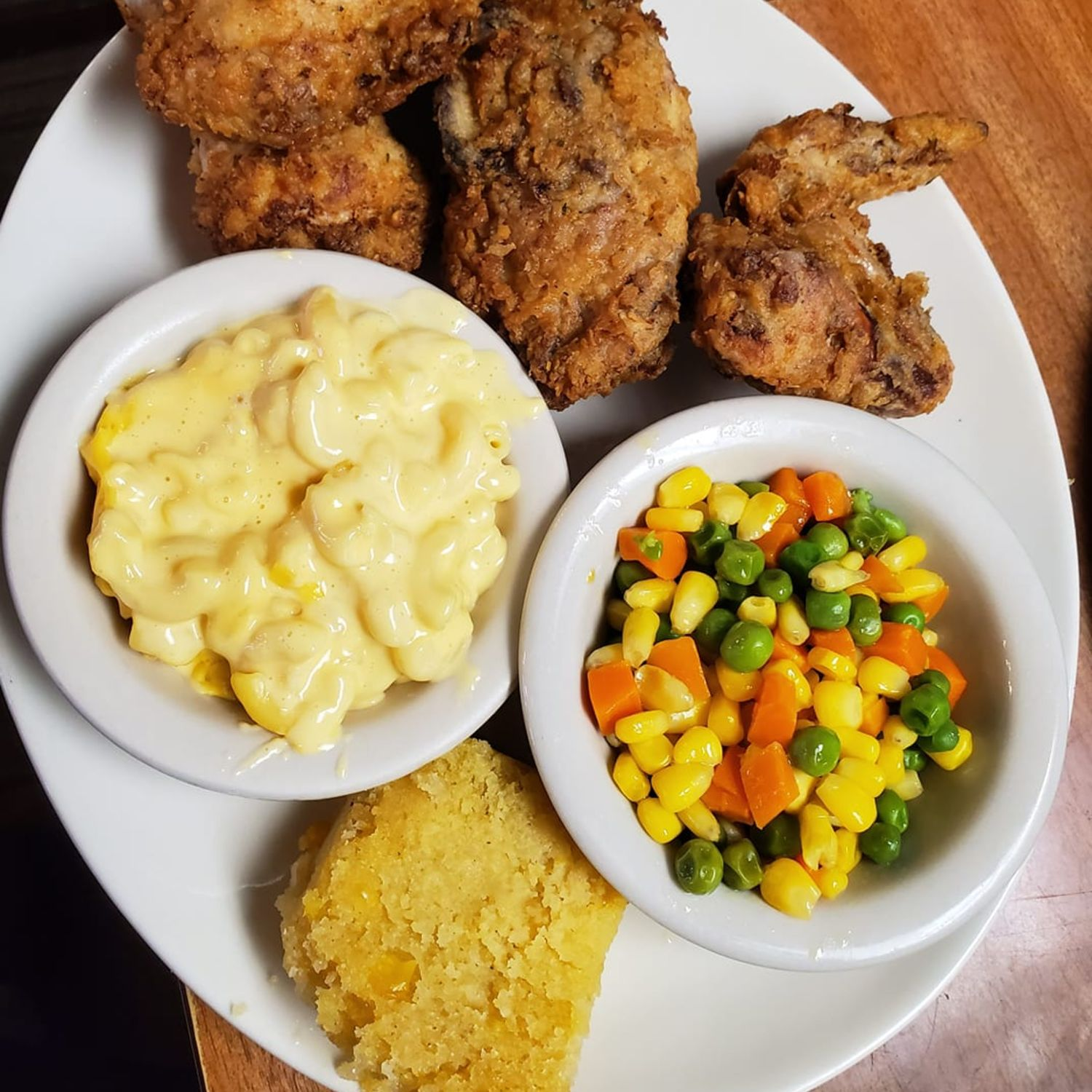 fried chicken, macaroni and cheese, mixed vegetables and a biscuit
