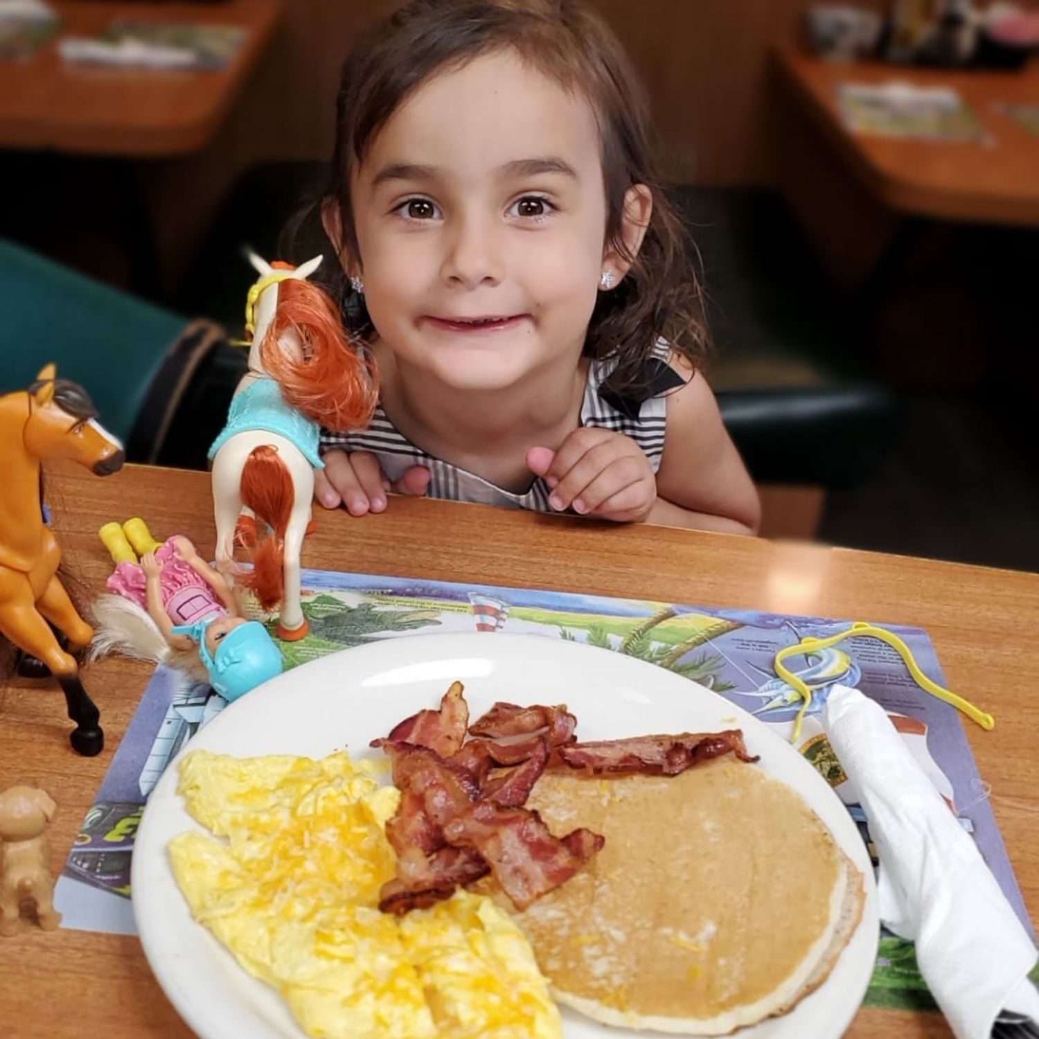 Girl posing for picture with plate of pancakes eggs and bacon