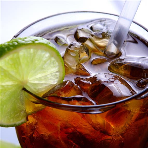 A glass filled with soda, ice, and a lime wedge on the edge of the glass