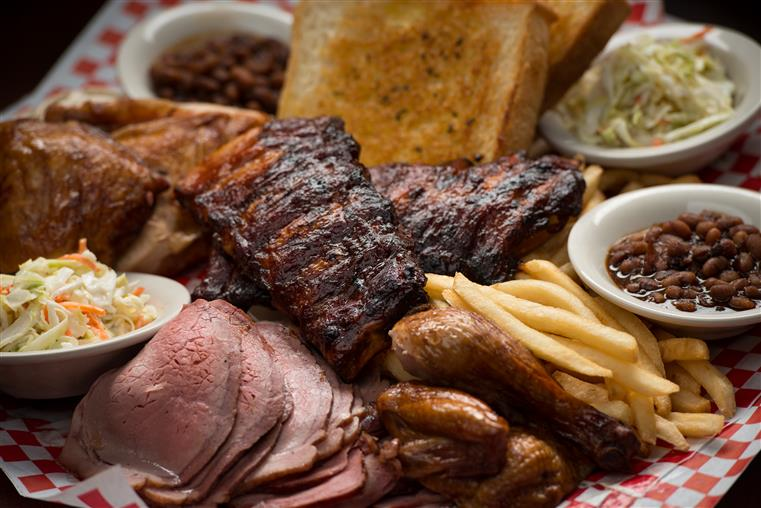 A BBQ platter filled with ribs, smoked ham, garlic bread, coleslaw, beans, and turkey