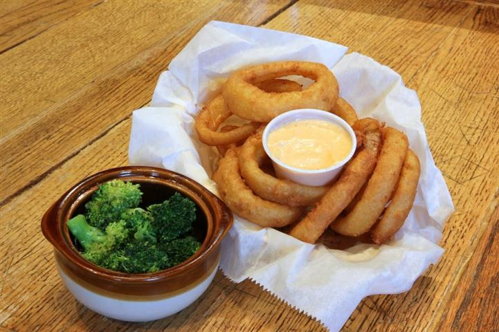 basket filled with onion rings and dipping sauce