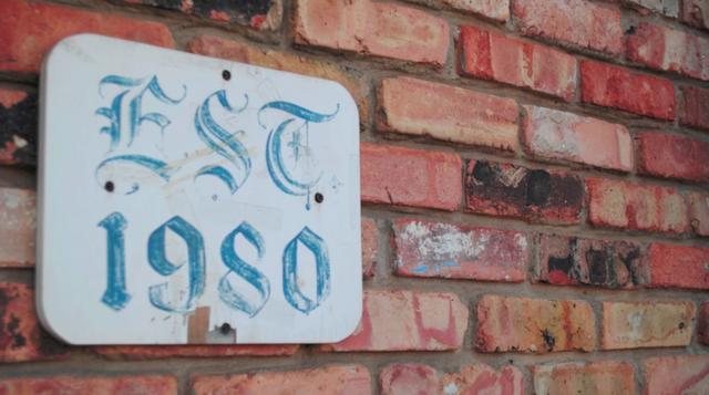 sign on a brick wall that reads est. 1980