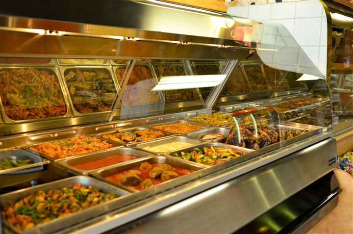 various buffet trays filled with assorted foods