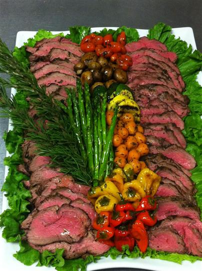 catering tray with sliced prime rib and various roasted vegetables with rosemary as a garnish