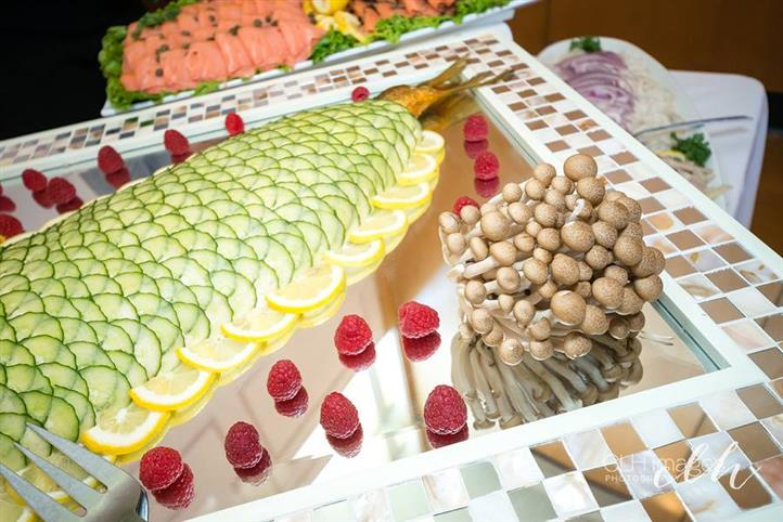 decorative catering tray with a whole smoked fish topped with thinly sliced cucumbers, lined with lemon slices. on a tray with a bundle of raw mushrooms and raspberries for garnish