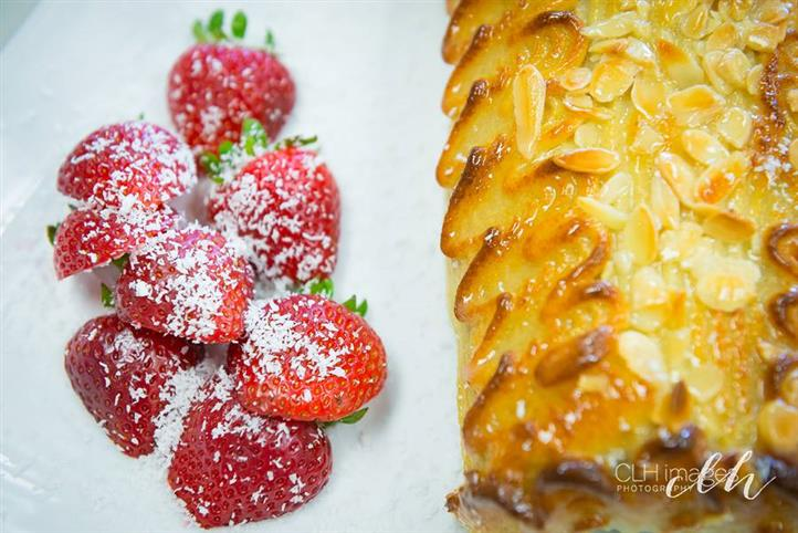 strawberries topped with powdered sugar and a pastry with apples on top