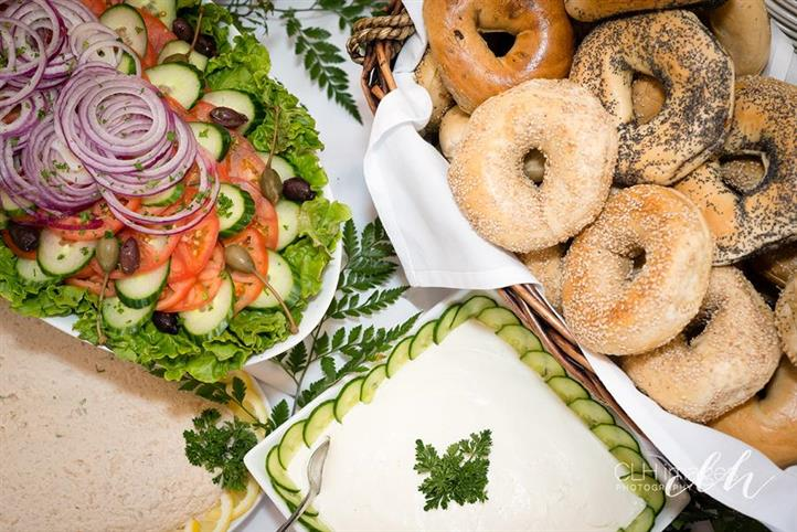 catering display with salad, bagels, cream cheese and other various toppings