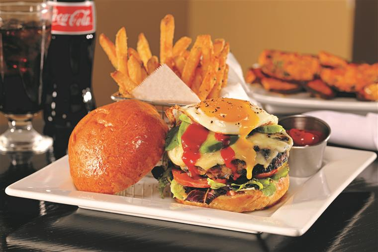 hamburger with melted provolone cheese topped with spring mix, tomato, avocado, hot sauce and a fried egg on a bun with a side of fries and ketchup