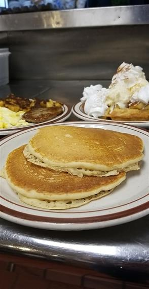 plate of a stack of pancakes with other breakfast food in the background