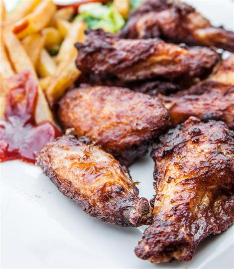 Barbecued chicken wings and french fries with ketchup