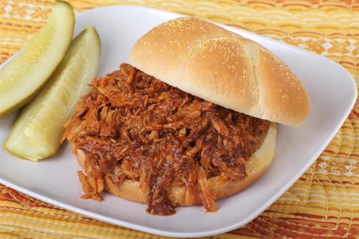 Shredded chicken sandwich with pickle slices to the side