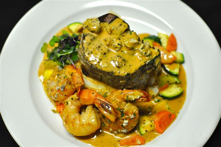 Steak and three shrimp topped with a creamy yellow sauce and served with mixed vegetables.