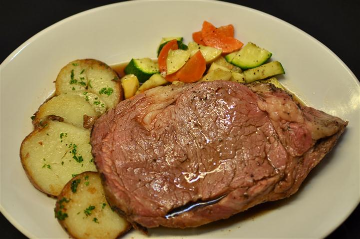 Cooked steak served with mixed vegetables and herb roasted potatoes.