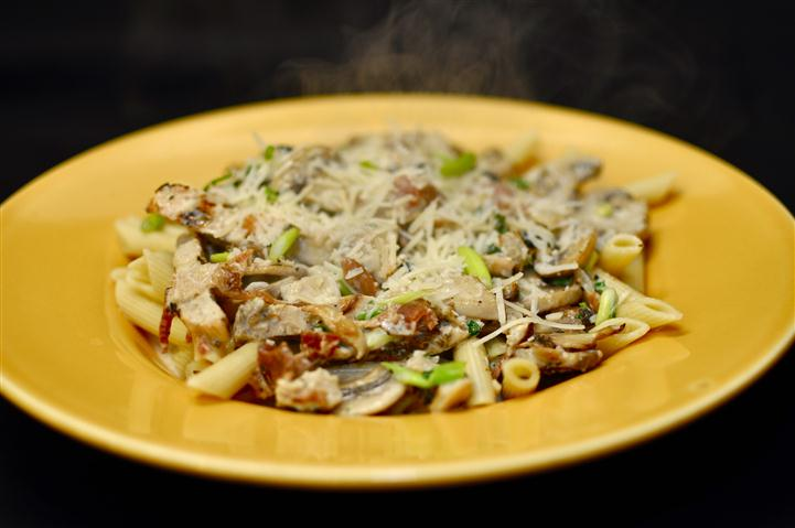 Penne pasta served with grilled chicken, mushrooms mixed in a creamy sauce.