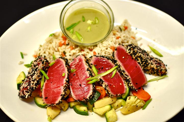 Ahi tuna with a side of rice and mixed vegetables served with a dressing on the side.