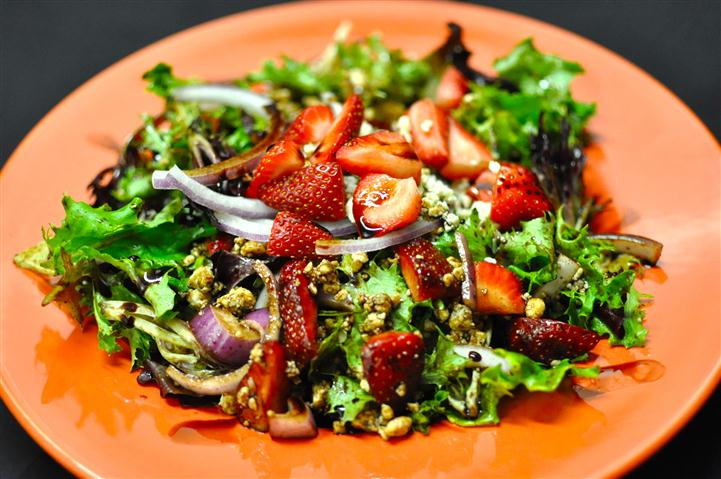 Salad with strawberries, red onion and a vinaigrette dressing.