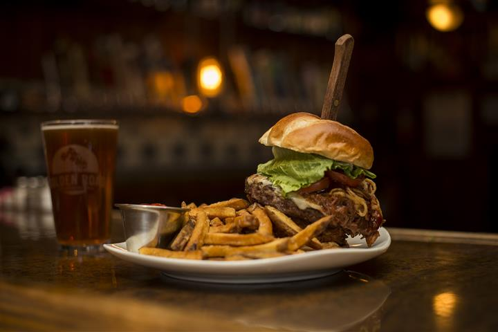 Cheese burger with a steak knife sticking in the top, topped with lettuce, tomato, caramelized onions and a side of french fries with ketchup. Served on the side is a pint of beer.