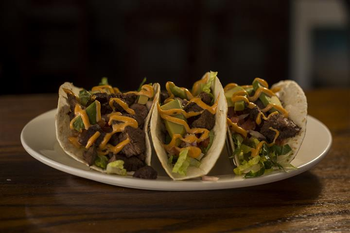 Three Steak House Tacos. Seasoned steak tips with a chipotle aioli, pico de gallo & avocado.