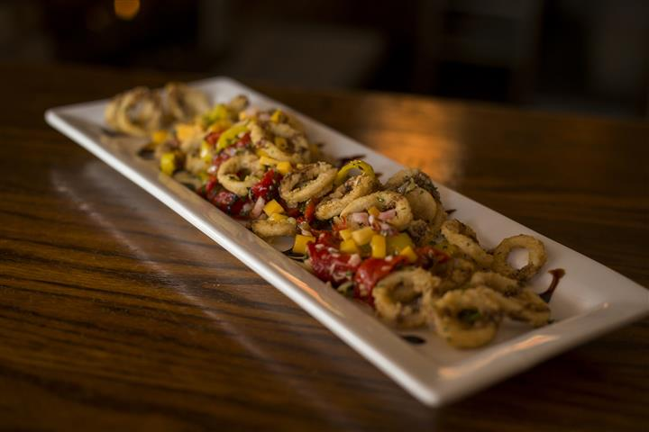 Plate of fried Calamari tossed with roasted red peppers, banana peppers, topped with mango salsa & a balsamic drizzle.