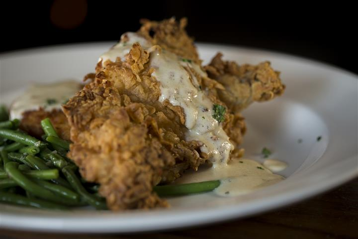 Fried chicken topped with Boursin cheese cream sauce served with a side of green beans.