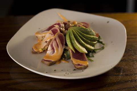 Plate of the Seared Tuna served with avocado slices and honey sriracha aioli.