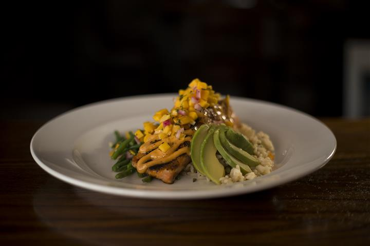 Blackened Grilled Salmon topped with avocado, mango salsa and lemon chipotle aioli served with rice pilaf.