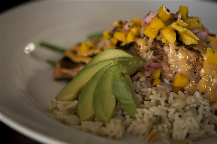 Close up of the Blackened Grilled Salmon topped with avocado, mango salsa and lemon chipotle aioli served with rice pilaf.