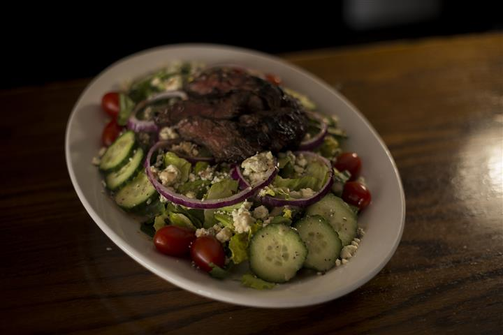 Donovan's Special salad, chopped romaine, with grilled hanger steak, red onions, tomato, blue cheese crumbles & roasted garlic red wine vinaigrette.