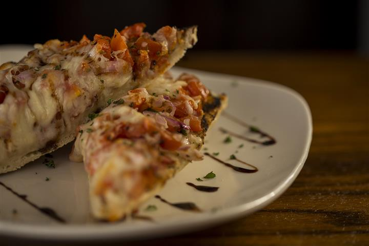 Plate of two pieces of bruschetta, Grilled French baguette, topped with diced tomato, red onion, garlic, mozzarella cheese and a drizzle of balsamic glaze.