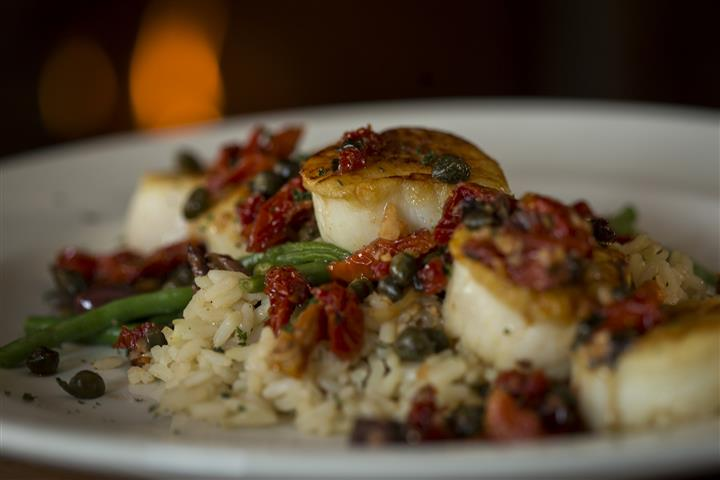 Close up of the Pan Seared Scallops with sundried tomatoes, garlic, capers, basil and kalamata olives served with rice pilaf.