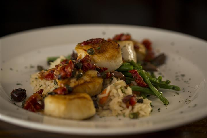 Pan Seared Scallops with sundried tomatoes, garlic, capers, basil and kalamata olives served with rice pilaf.