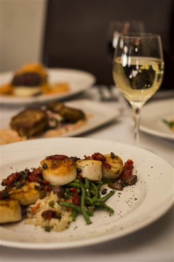 Pan Seared Scallops with sundried tomatoes, garlic, capers, basil and kalamata olives served with rice pilaf with a glass of white wine.