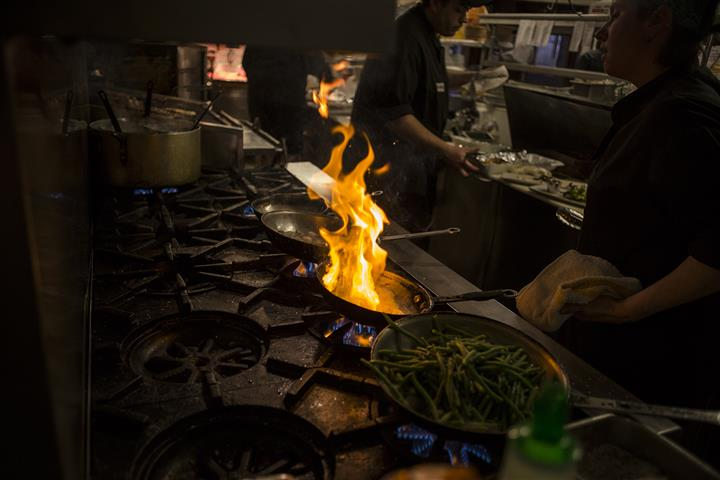 View of stove top with 3 pans, one with green beans and the other with flames.
