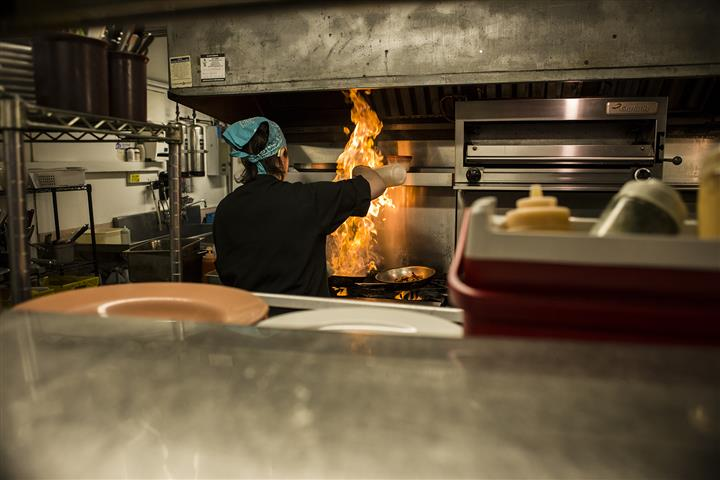 Chef in front of the stove top with flames.