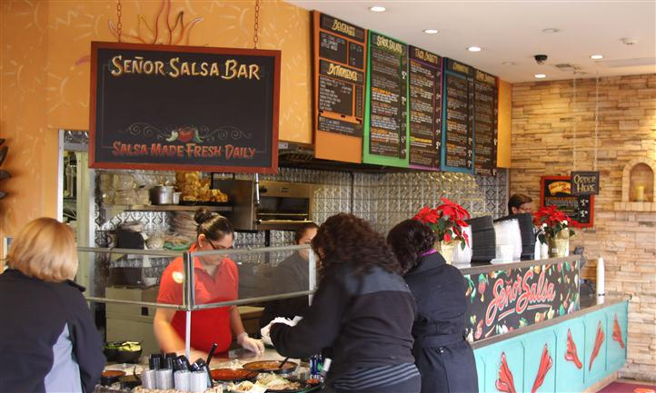 Salad bar counter with staff serving people