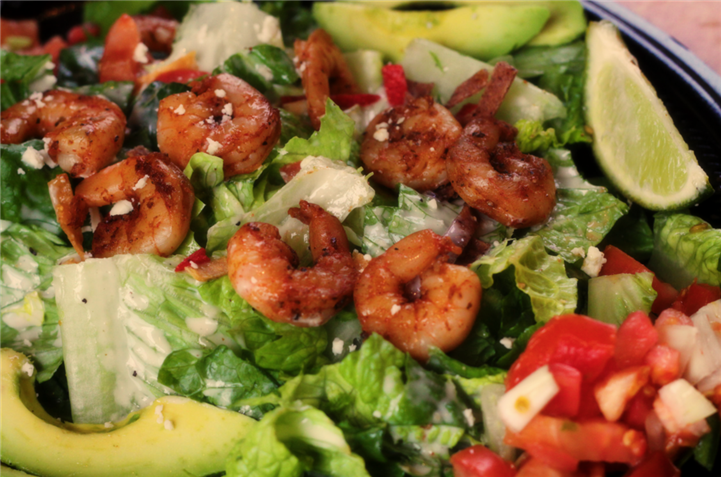 Salad topped with fried shrimp