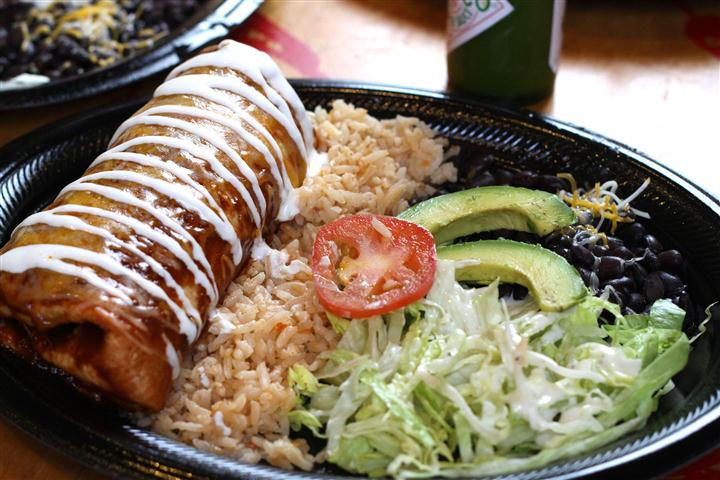 Burrito served over rice and sliced avocado with salad