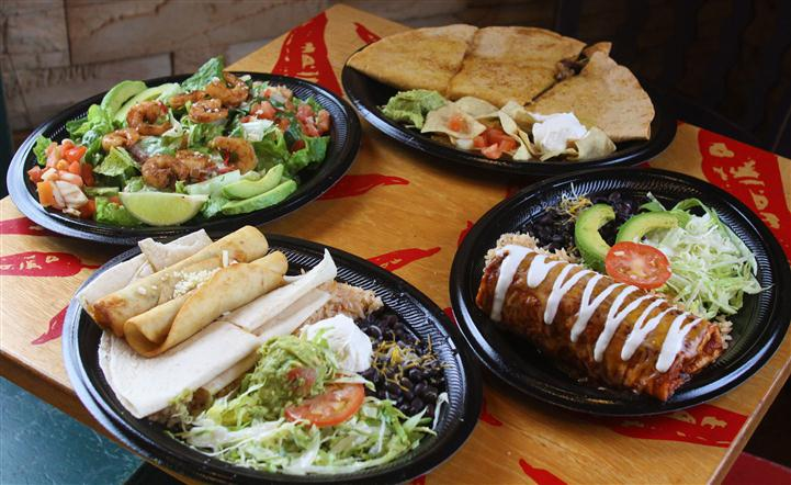 Mexican main dishes served for dinner on big plates with salad on the side