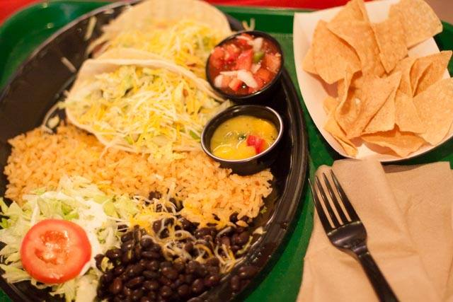 Taco plate served with rice and dips on the side with tortilla chips