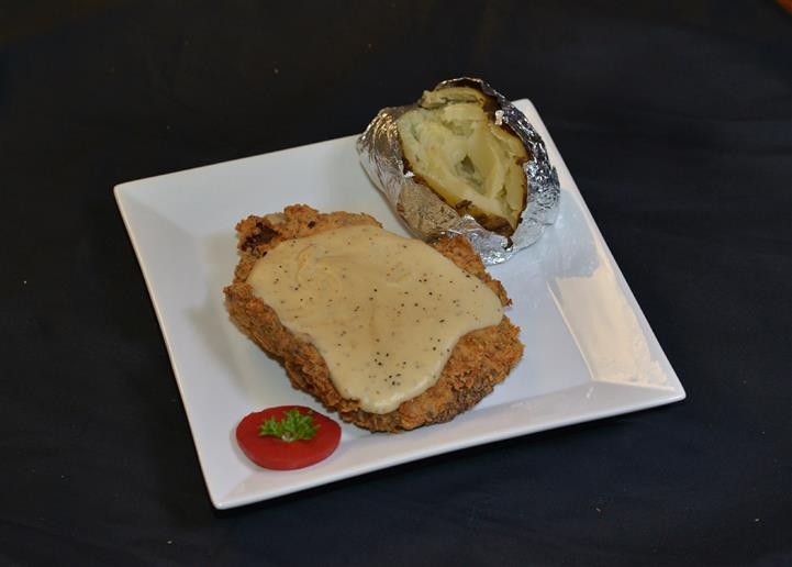 country fried steak topped with gravy with a baked potato